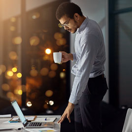 Lone male office worker in a dark office at night with a realtime tracking device fitted